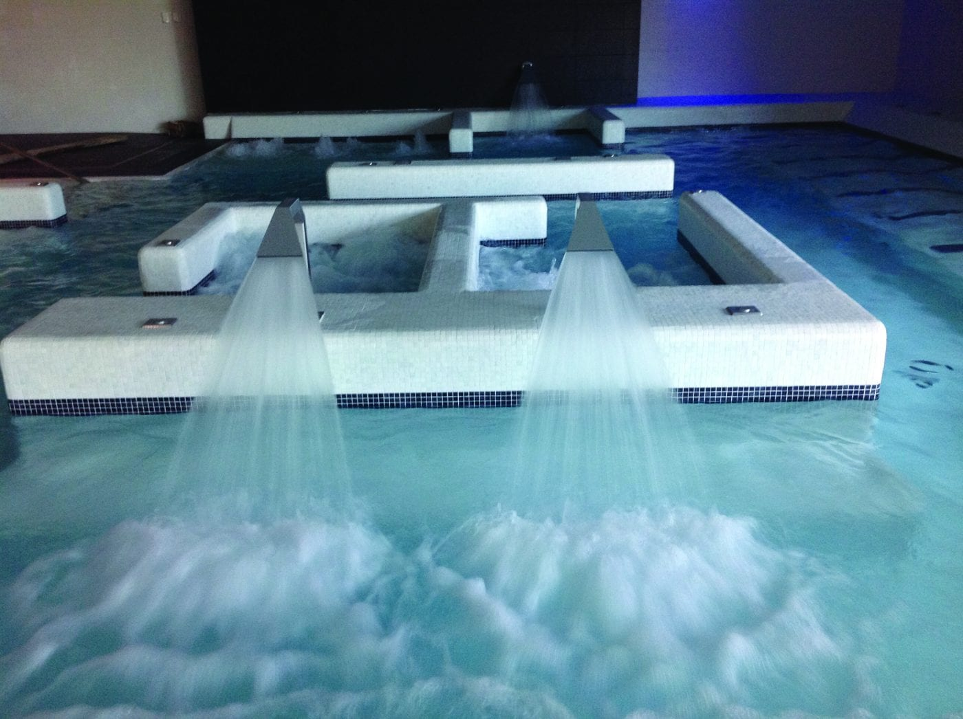 Stainless steel nozzle fountains flowing into indoor pool