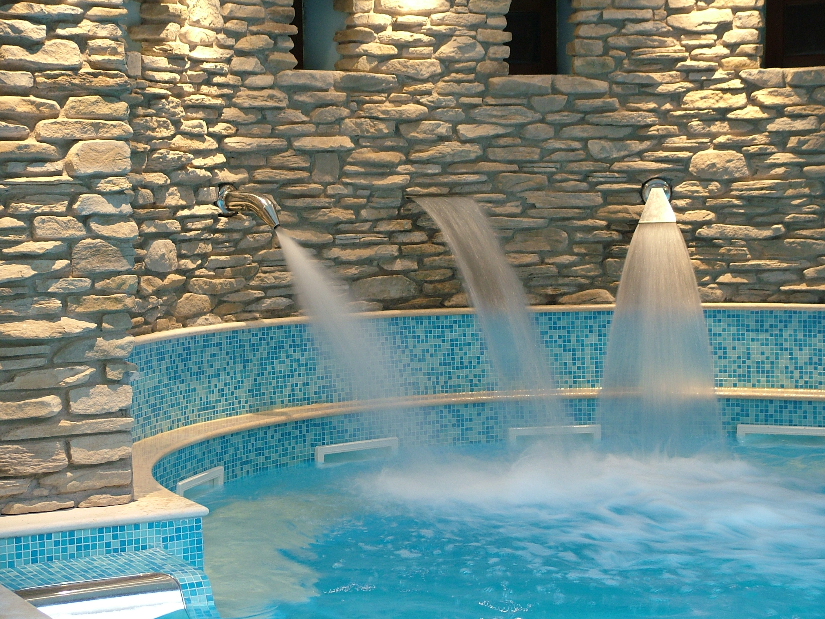 Swimming pool with stainless steel wall mounted water fountains